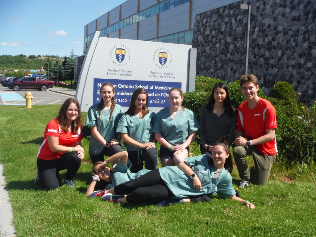 Campers and team leads pose for group photo outside in front of Northern Ontario School of Medicine sign. Two campers lay on ground in front of group while other team members kneel on one knee