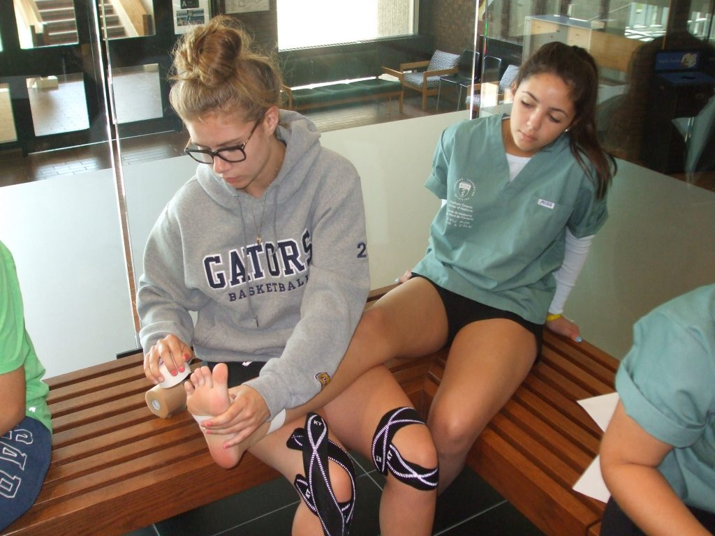 Camper sits on bench and props leg up on fellow campers lap while they wrap tape around the ankle