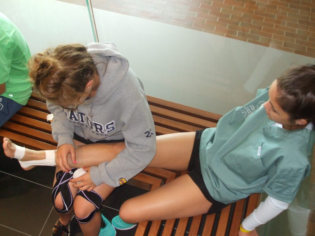 Camper applies supporting tape to fellow campers ankle