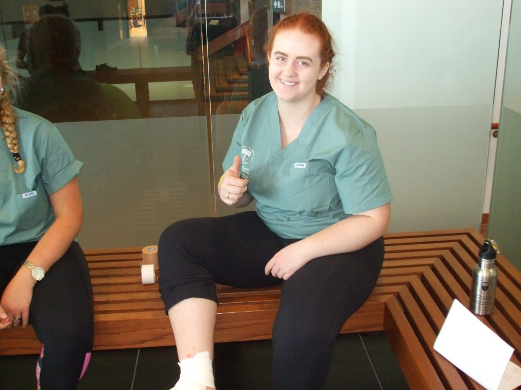 Camper sits on bench and gives thumbs up after having ankle taped