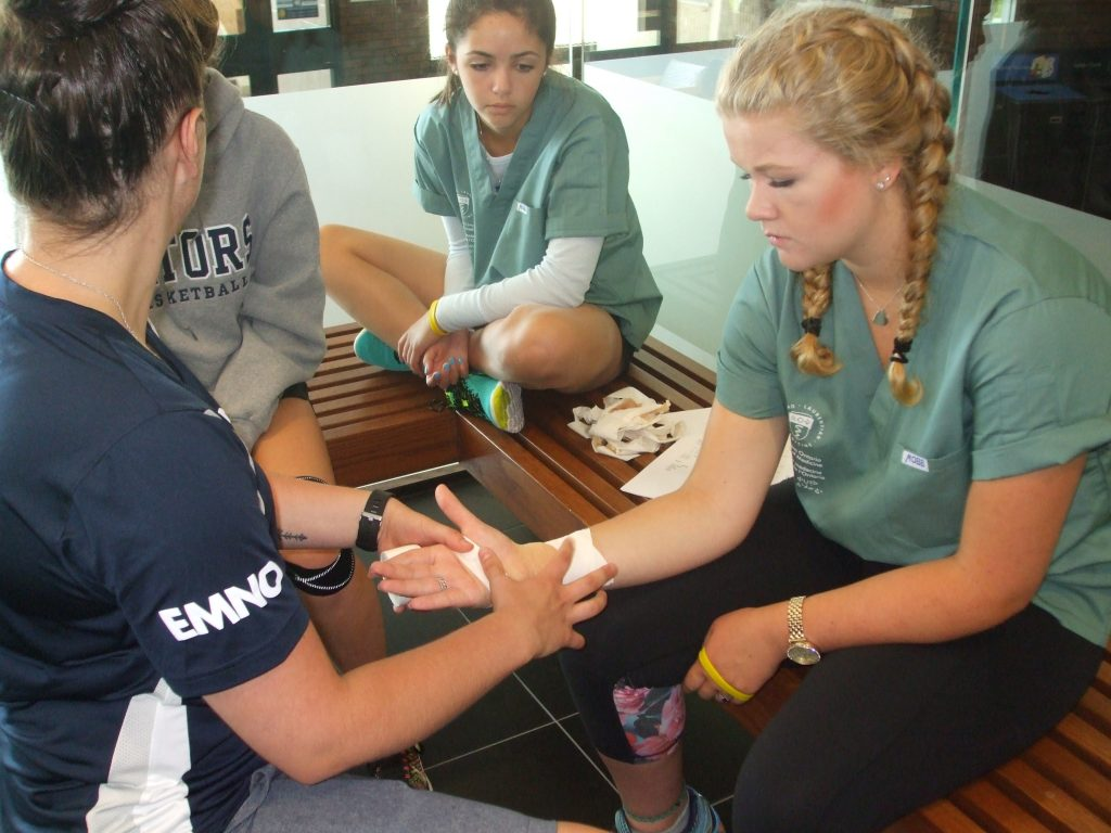 NOSM Staff member demonstrates how to wrap tape around a campers wrist and hand while two campers look on