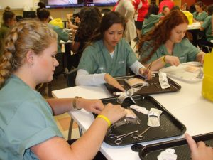 Three campers sit around table in lab practicing suturing techniques