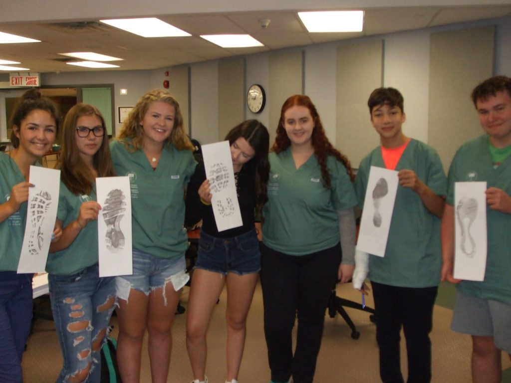Campers pose for a group photo and display their footprint analysis cards in classroom