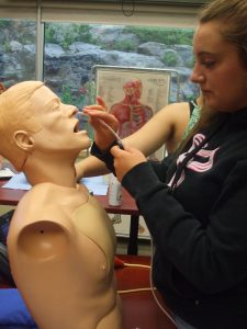 Camper inserts naso-gastric tube into SimMan mannequin bust in small group room