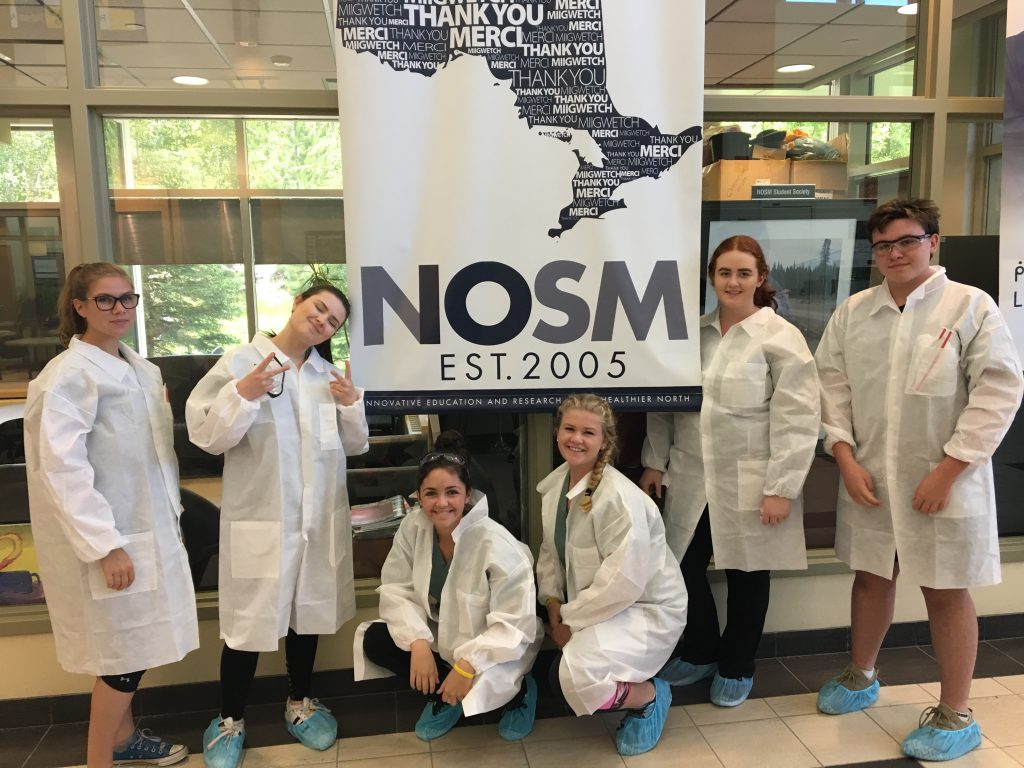 Campers pose in front of NOSM Est. 2005 banner in medical school lobby while wearing their CSI coats and booties