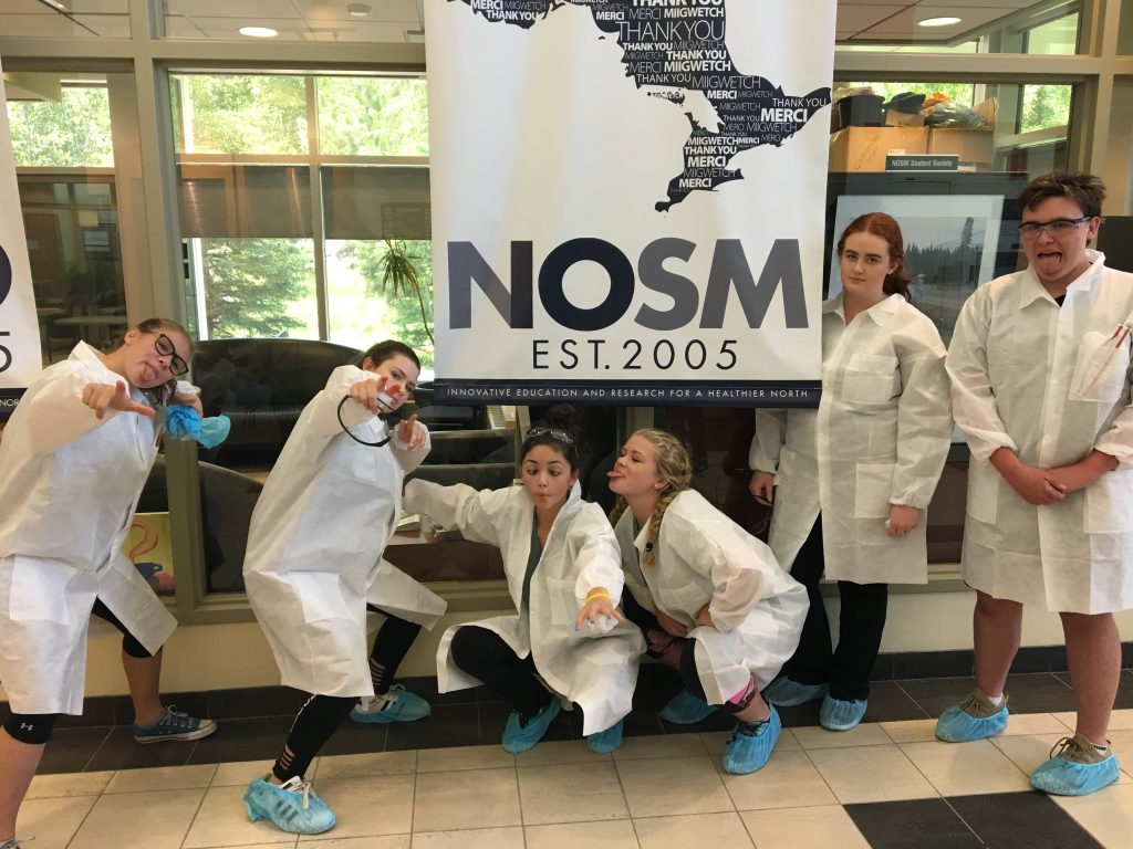 Campers strike funny pose for group photo in front of NOSM Est. 2005 banner while wearing their CSI coats and booties