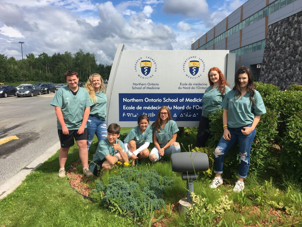 Camper team poses for group photo outside in front of the Northern Ontario School of Medicine sign