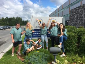 Camper team strikes funny and fun poses for group photo outside of medical school building in front of the Northern Ontario School of Medicine sign