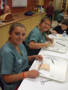 Two campers pose for photo while practicing suturing techniques