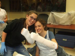 Two campers give thumbs up with their casted arm hands