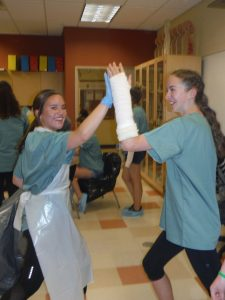 Camper with casted arm high fives a camper wearing blue latext gloves in lab