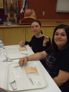 Two campers pose for photo while practicing suturing technique