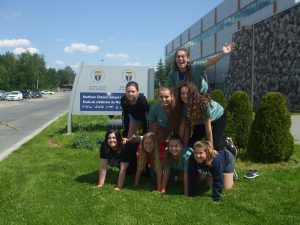 Campers and team lead create human pyramid outside in front of Northern Ontario School of Medicine sign