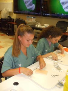 Campers practicing suturing technique intently