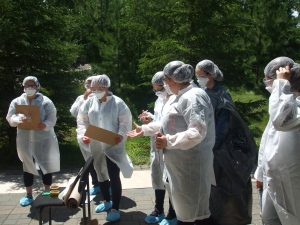 Campers wearing CSI protective coats, caps, masks, and booties stand outside preparing for CSI activity