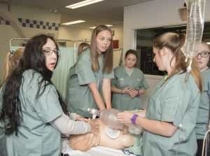 Camper performing CPR on SimMan 3G simulation mannequin while two fellow campers ventilate and other camper looks on in background
