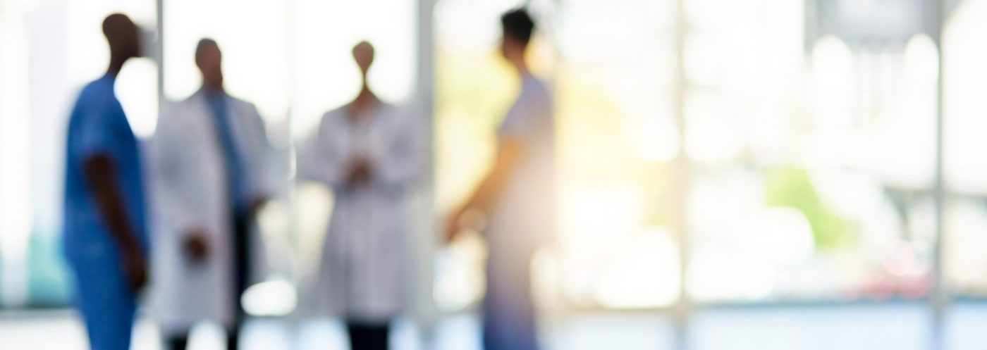 Blurred shot of a team of doctors standing together in a clinical setting