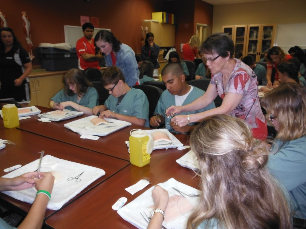Retired surgeon instructs campers on suturing technique