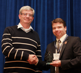 Photo of Dr. David Boyle receiving an award, shaking hands with the award presenter