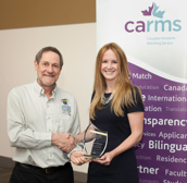Photo of Dr. Sarah McIsaac receiving an award, shaking hands with the NOSM Associate Dean, Dr. Roger Strasser.