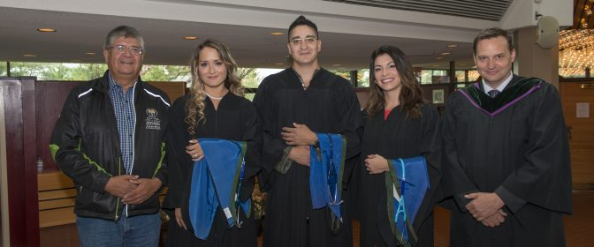 Photo of three Indigenous MD Graduates with an Elder and a NOSM Associate Dean on graduation day.