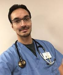 Photo of Kevin Brousseau in scrubs with a stethescope around his neck.