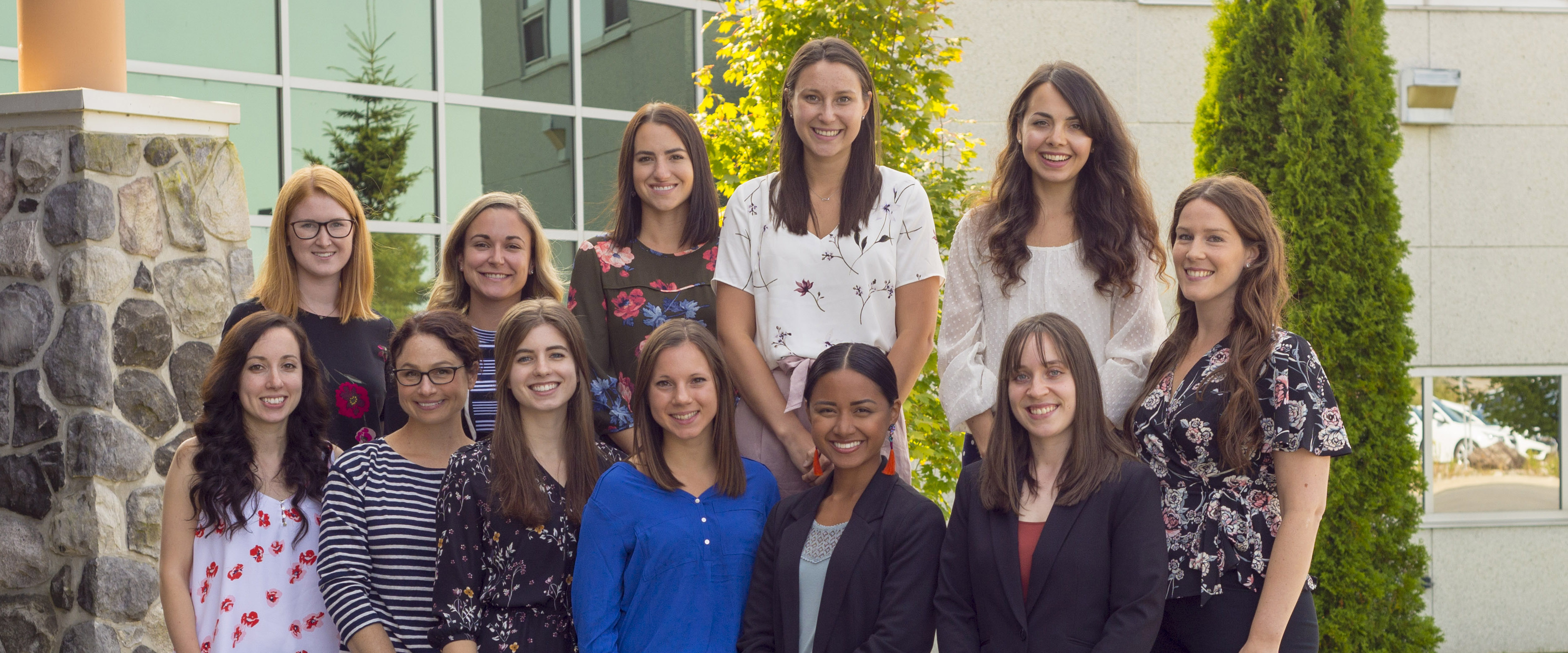 Photo of 12 dietetic interns sitting or standing on the rocks near the front of the medical school building in Sudbury.
