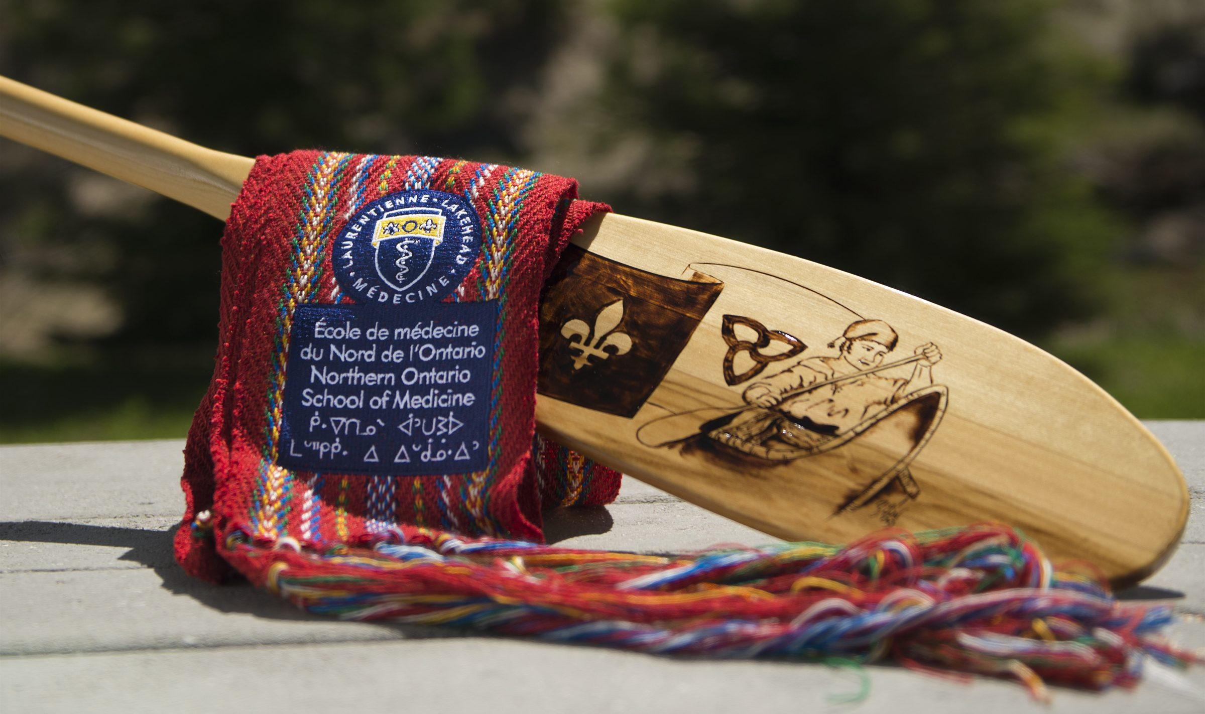 Photo of voyageur sash and wooden oar.
