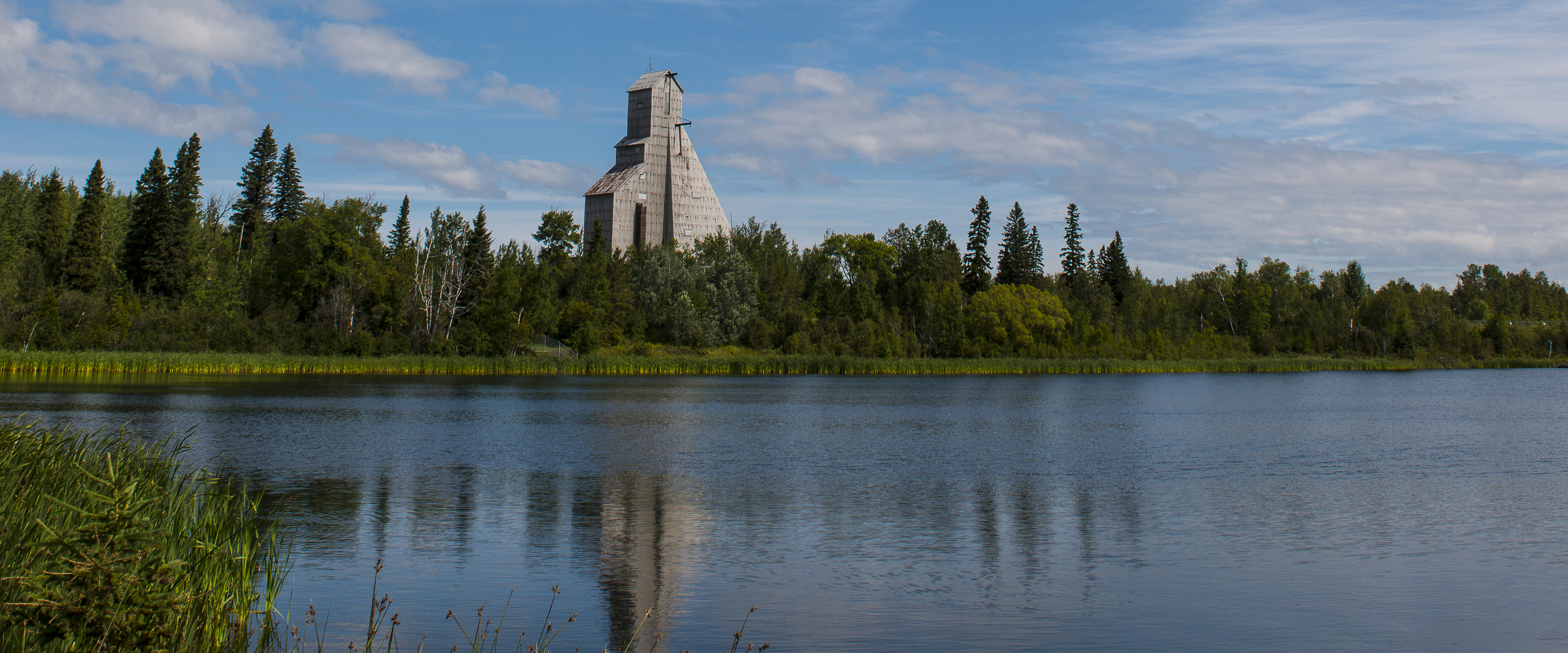 Photo of a lake in Timmins, Ontario, with a mine headframe in the background.