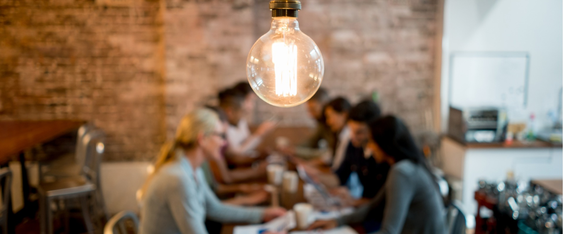 A group of health professionals working together around a table. A lightbulb hangs over their heads.