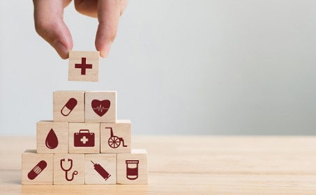 Hand arranging wood blocks with health care icons on the blocks.