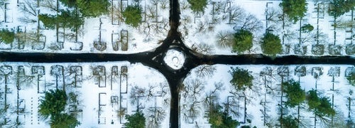 Roundabout with four roads leading in different directions amoung snowy fields with trees