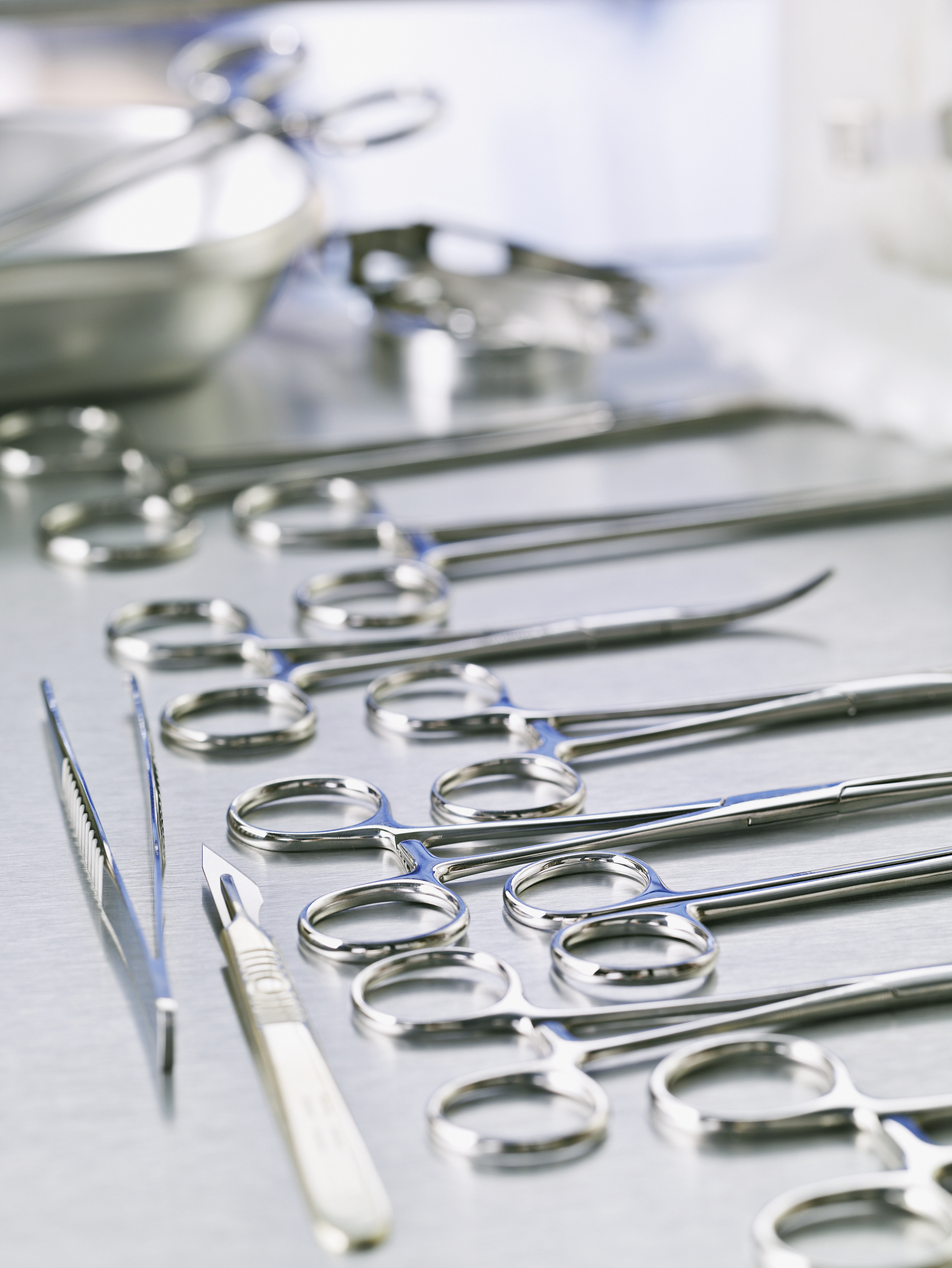 Medical scissors and scalpel on surgical table.
