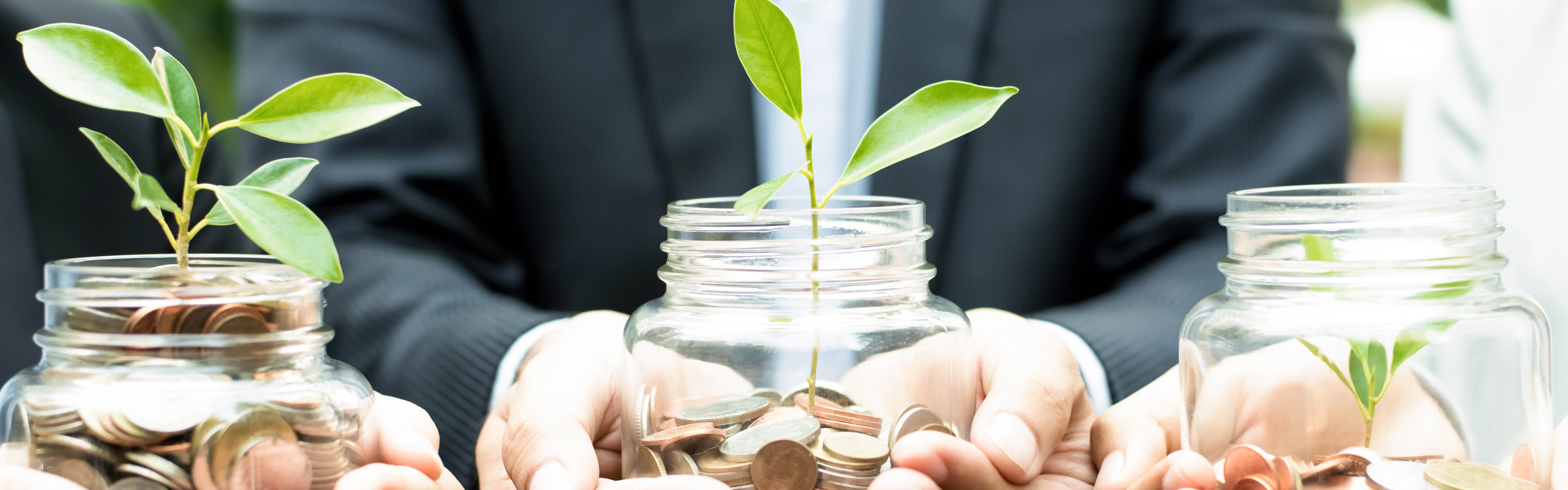 Photo of tree saplings growing out of mason jars. Rather than soil, the mason jars have coins in them. This represents how the areas of giving can flourish when we all support NOSM's goals.