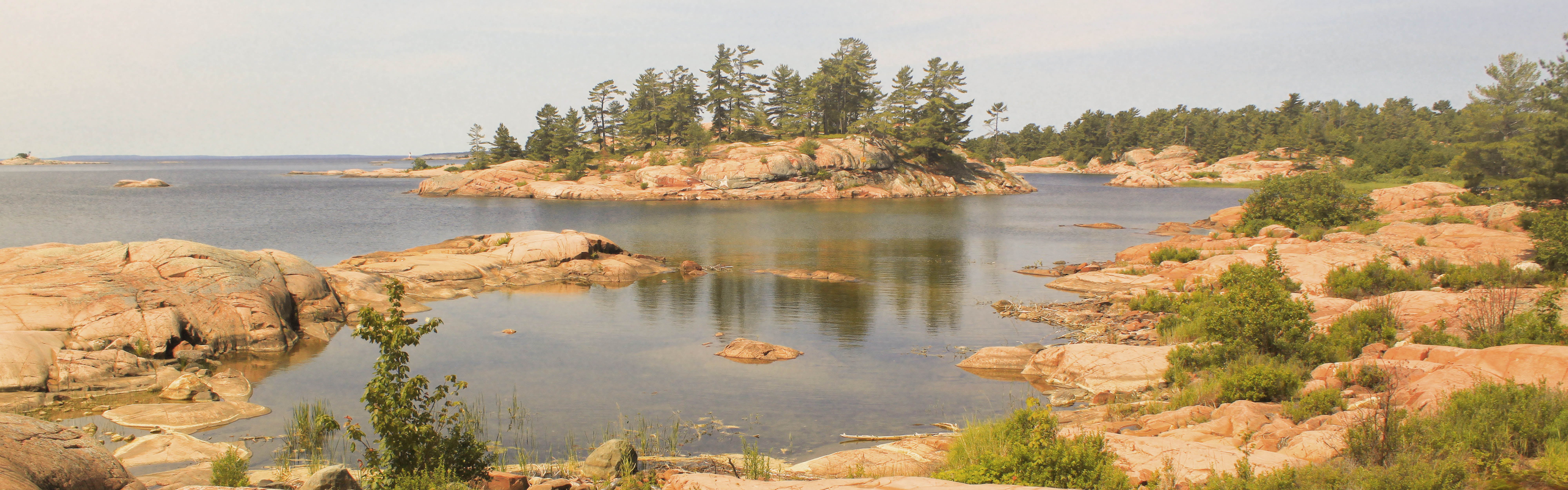 Photo of Northern Ontario Lake, with a rocky shoreline and large pine trees off in the distance.