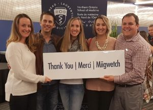 Group of five NOSM MD graduates holding a sign that says thank you, merci, and miigwetch.
