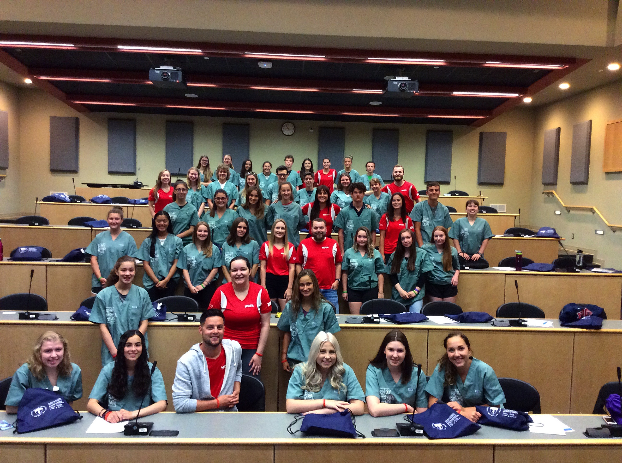 Group photo of all campers and team leads in large lecture hall classroom