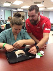Team lead supervises camper practicing suturing technique