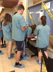 Campers wearing blue booties prepare to enter staged crime scene area