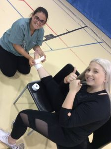 Camper sits on chair in gymnasium while fellow camper kneels on floor and wraps their ankle