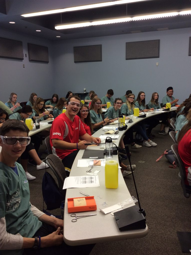 Group photo of campers learning to suture in large classroom