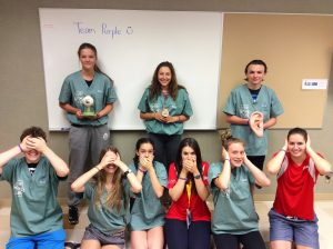 "Team Purple re-enacts the Three Wise Monkeys ""See no evil, Speak no evil, Hear no evil"" pose; three campers hold an eye model, a tongue model, and an ear model while fellow campers and two team leads cover their eyes, mouths, and ears with their hands"