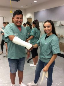 Two campers pose for photo; one camper displays casted arm