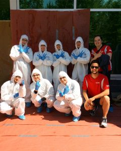 Camper group wearing white painter's coveralls, blue gloves, and safety glasses pose outside with two team leads during CSI blood spatter analysis activity