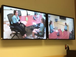Photo of dual videoconferencing TV monitors displaying two angles of two campers sitting at table