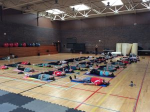Campers and team leads lay on backs no yoga mats in gymnasium