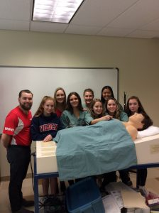 Camper group and two team leads pose with SimMan 3G mannequin in clinical skills room
