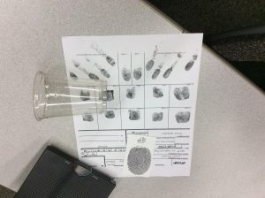 Photo of a fingerprint analysis activity sheet and clear plastic cup