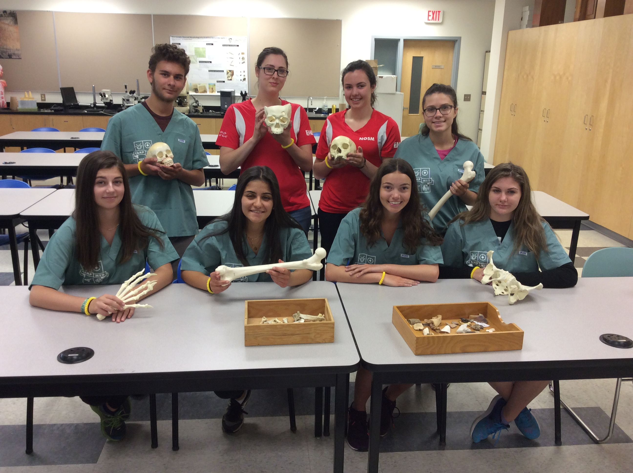 Camper group and two team leads pose for photo holding skull, arm, hand, and leg, and pelvis bone models in anthropology classroom