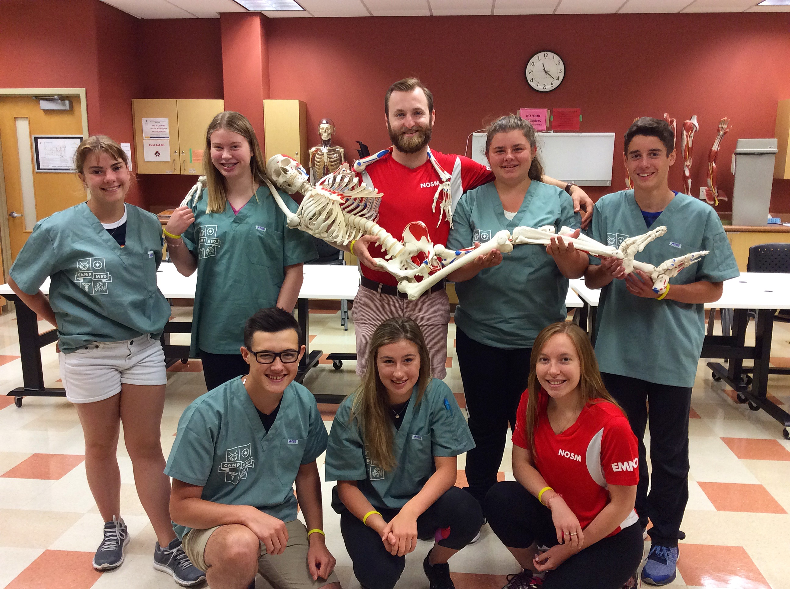 Camper group and two team leads pose with skeleton model in clinical skills lab